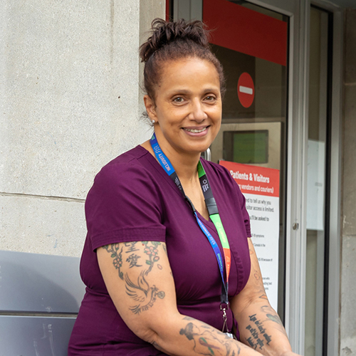 A health care worker wearing scrubs and a lanyard with an identification badge stands outside a hospital looking at the camera smiling