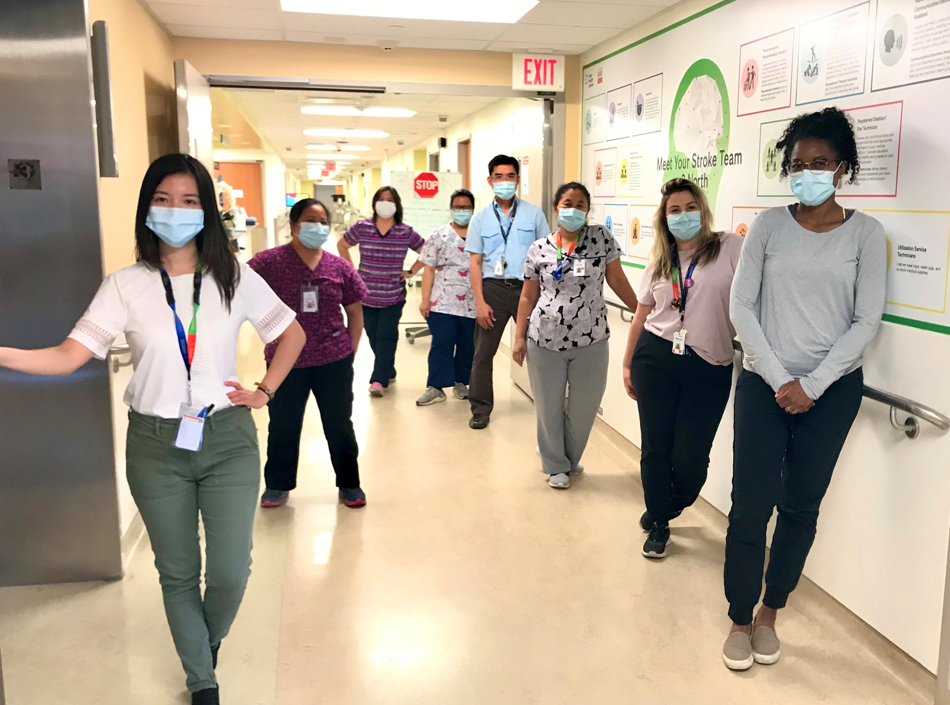 A group of health care workers standing in the hallway of a hospital. They are wearing masks and some are wearing scrubs. They are facing the camera