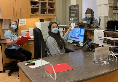 a Photo of health care workers in an office at a reception desk. they are wearing masks and looking at the camera.