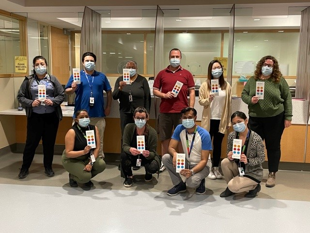 A team of 10 healthcare professionals in a group. They are wearing masks and each holding up a brochure and looking at the camera.
