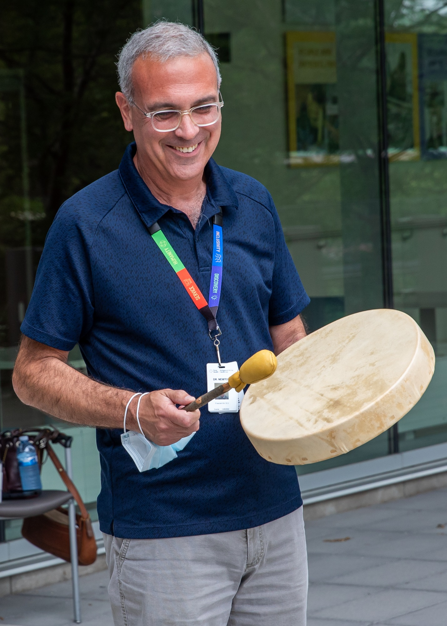 A man is smiling while holding and playing an Indigenous ceremonial drum