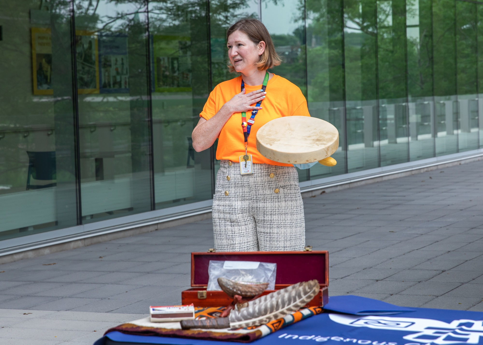 A woman in an orange shirt holds an indigenous ceremonial drum. Materials used for a smuding ceremony sit on a table in front of her
