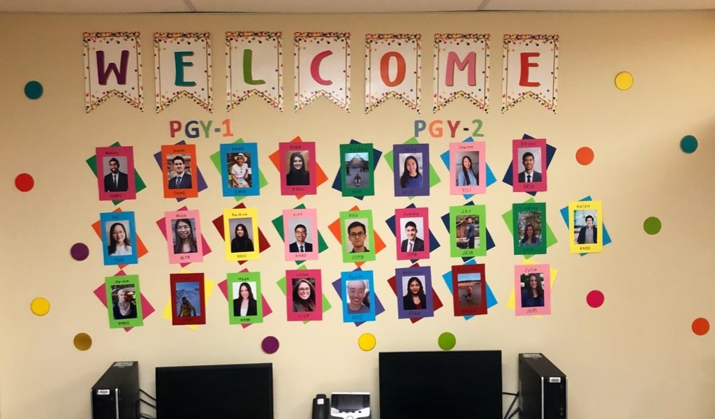 """Colourful display posted on a wall. It says """"Welcome"""" at the top and then has rows of photos of new residents joining the Family Medicine team. Each photo has a colourful frame"""