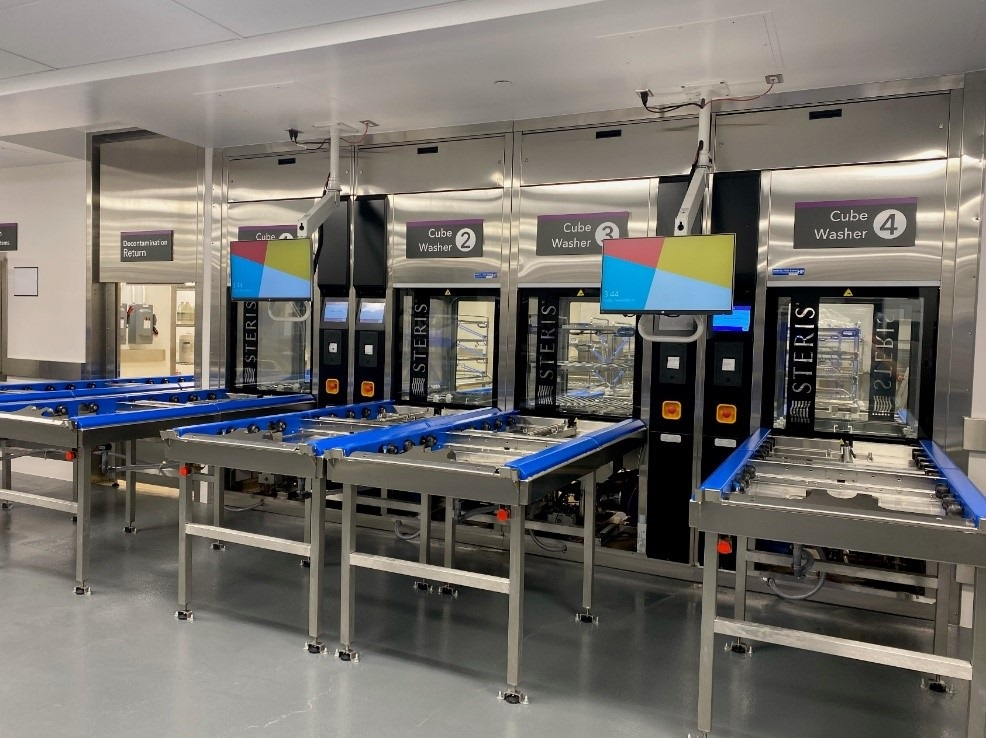 A medical device reprocessing room in a hospital. The room has four of the same machines. Each one has a sign that says Cube Washer, numbered one to four. The room is otherwise empty