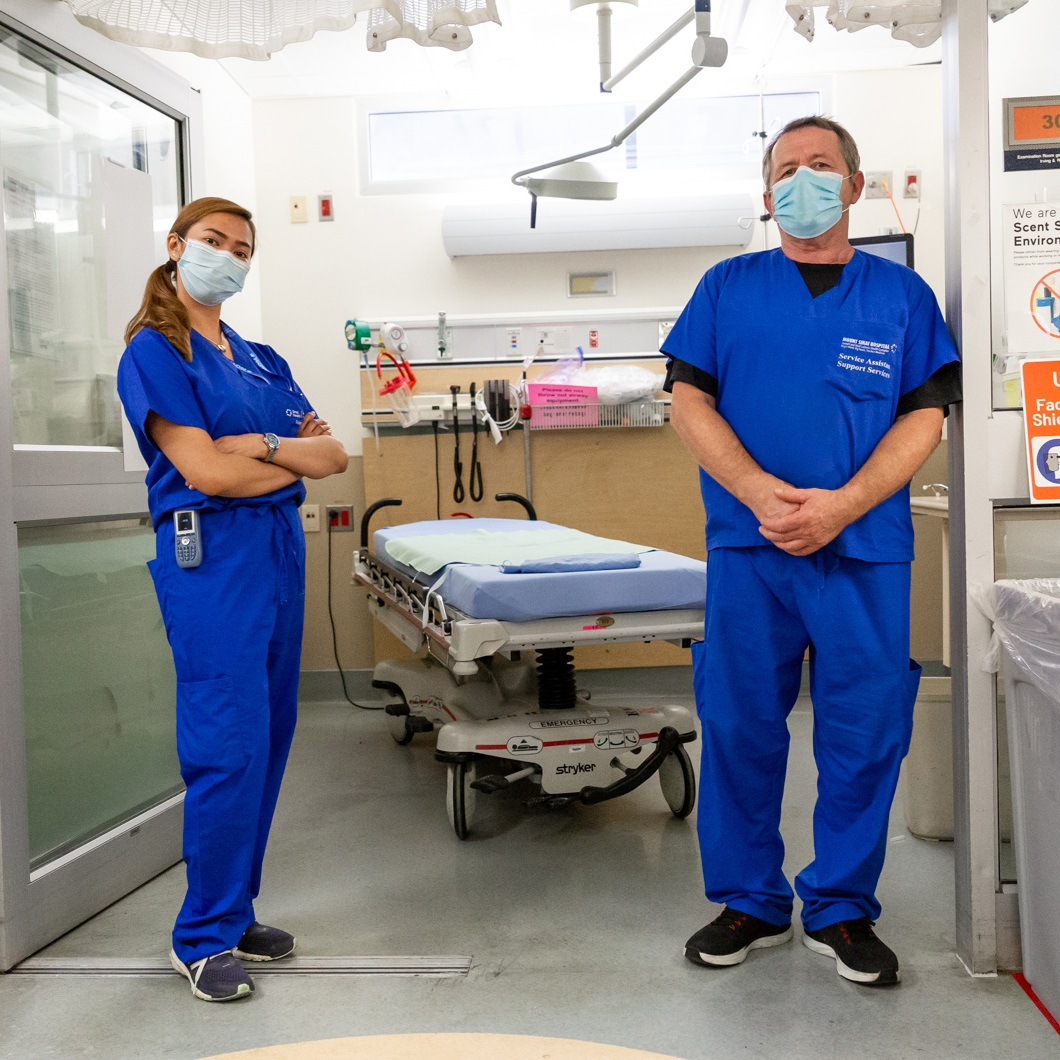 Two hospital employees on the Environmental Services team standing in front of a room in the Emergency Department. Both are wearing blue scrubs and procedure masks and they are facing the camera