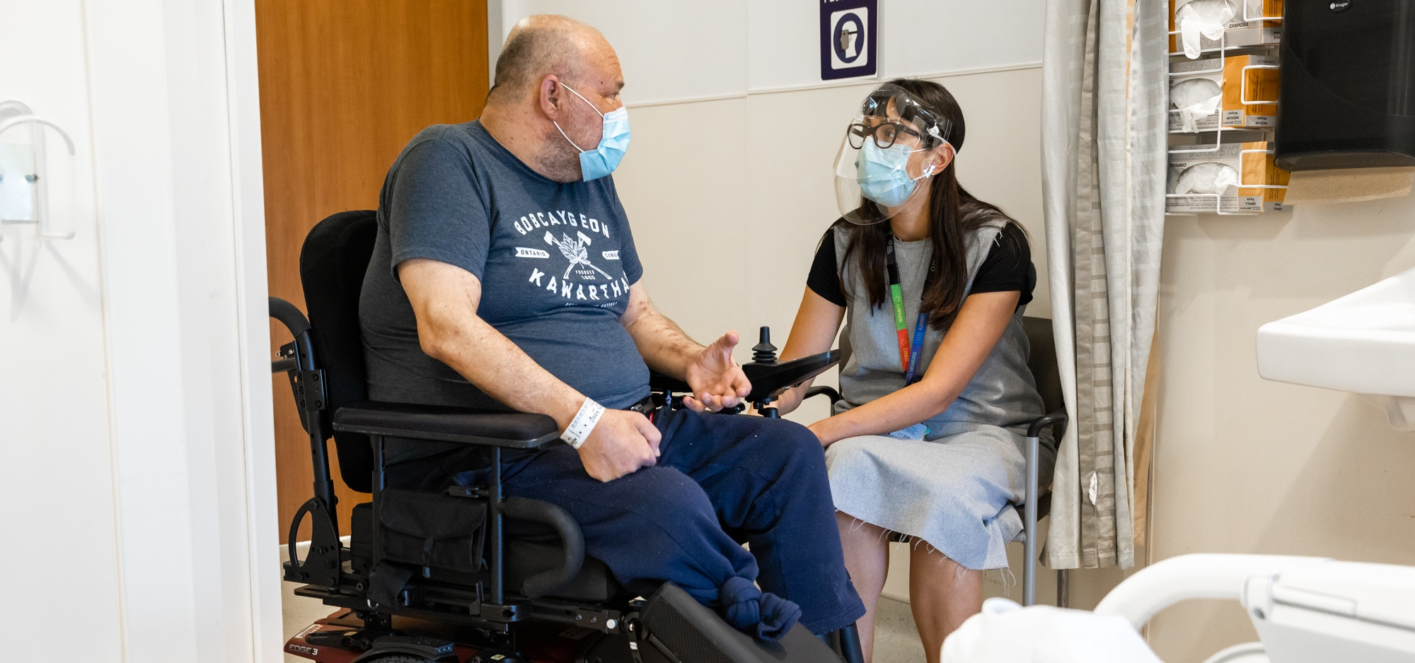 A patient who is in a wheelchair is sitting in a hospital room and talking with a health care worker. The patient is wearing a procedure mask and the health care worker is wearing a procedure mask and face shield.